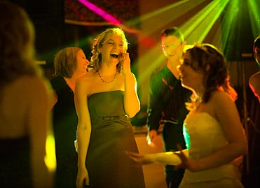 Celebrate: Guests dancing against disco strobe lighting effect backdrop.