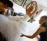 Preparing: Bridesmaids help the bride with her dress.