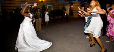 Night time scene: Bride throws her bouquet to anticipating guests.