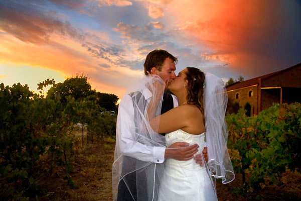 bride and groom kiss in vineyard at sunset in Barossa Valley Australia