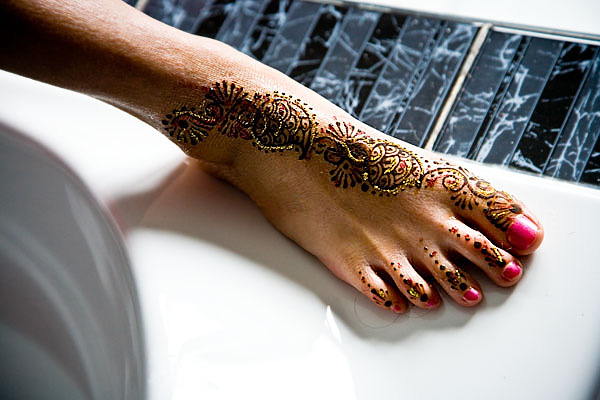 Sikh bride's foot decorated with henna and red-gold glitter