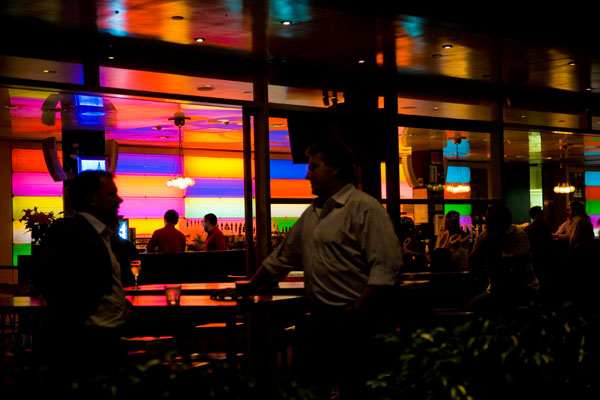 shadowy passers by the colourful buildings in Sydney at night
