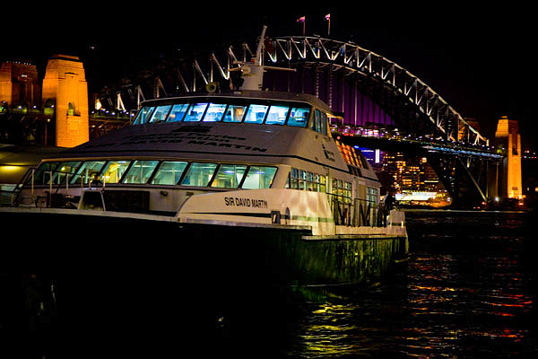 Sydney bridge and ferry boat at night