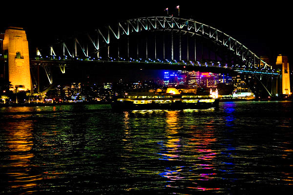 Sydney Bridge sparkling into the water at night