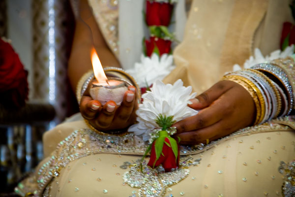 Hindu bride's hands with candle during wedding ceremony