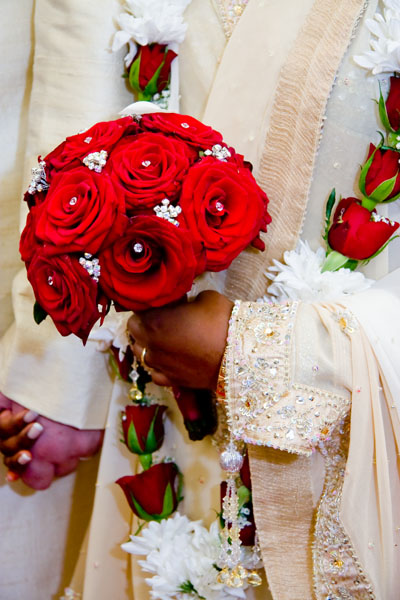 Hindu bride and groom with bouquet of red roses