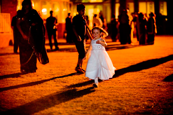child running in the dark at Hindu evening wedding ceremony