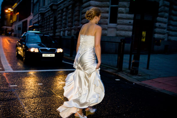 rainy day wedding picture with bride rushing across the road at night