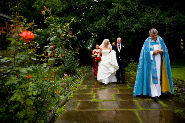 rainy day wedding with wet sheen on stone church pavements