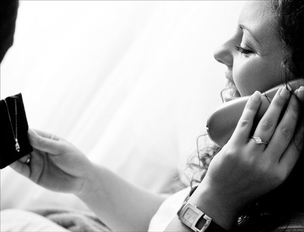 Black & White photo of bride in on phone as receives wedding jewellery gift