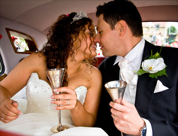 bride & groom about to kiss inside wedding car