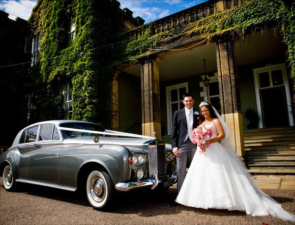 bride and groom arrive at Woolley Hall wedding venue in classic car