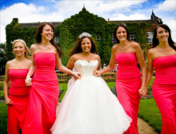 close up of bride and bridesmaids running in grounds of Woolley Hall
