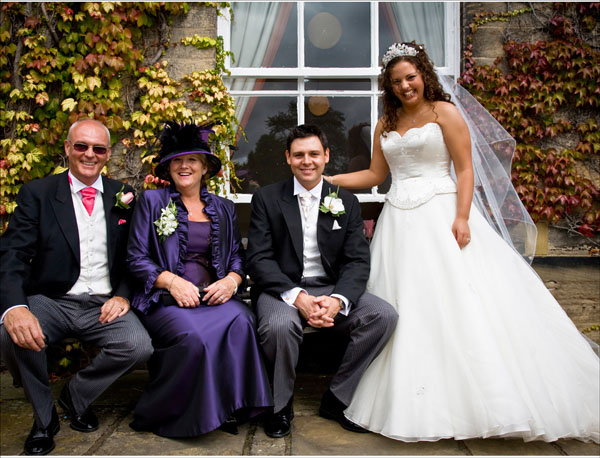 Groom's family on bench outside back of Woolley Hall