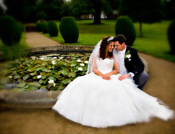 bride and bridegroom by lily pond in grounds of Woolley Hall in August 2008
