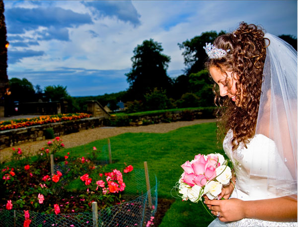 bride looking down at her bouquet late evening at Woolley Hall