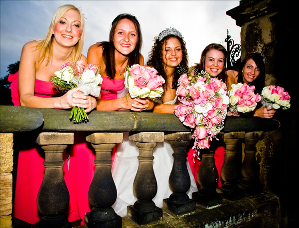 bridesmaids leaning over balustrade at Woolley Hall