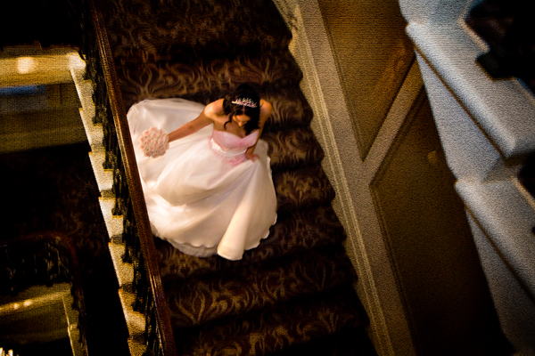 bride photgraphed from above as she descends the grand staircase