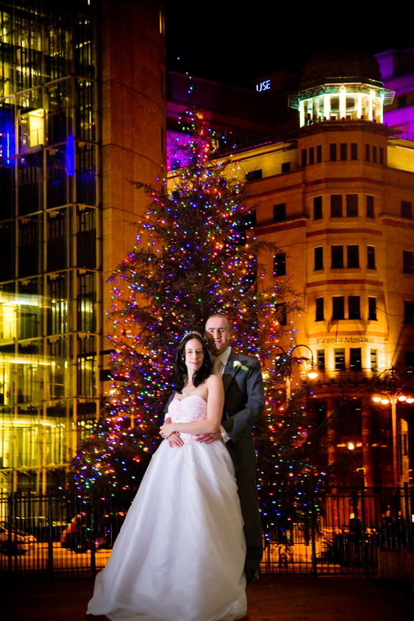 bride and groom by Christmas tree in Leeds City centre on wedding day