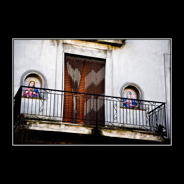 white-painted Italian house with Catholic Icons in Balcony alcove windows