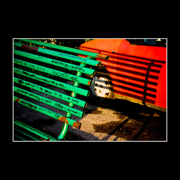 abstract art picture of green grafitti-covered bench against red car in Benevento