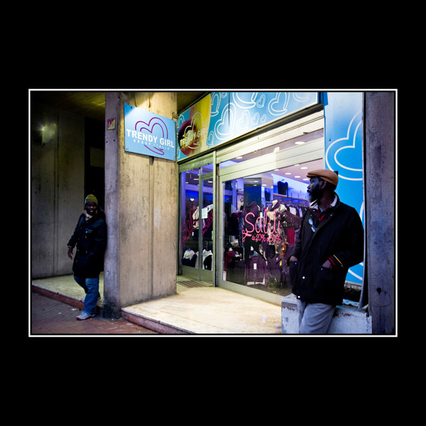 two black guys hang out at night by a Trendy Girl clothes shop in Benevento, Italy