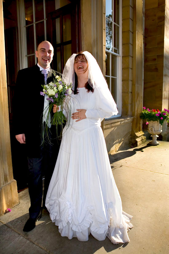 bride and groom laughing outside entrance to Oulton Hall Hotel
