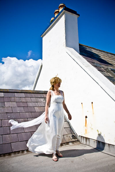 bride risks her tidy hair in wind on rooftop before descending form the ceremony