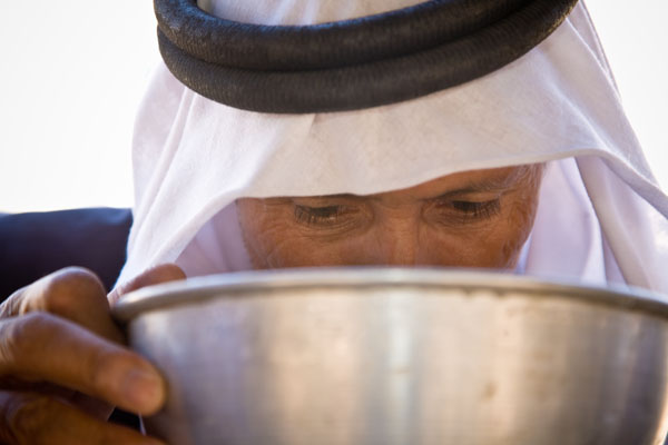 Bedouin man drinks from a shared metal bowl at wedding in a tent in Petra