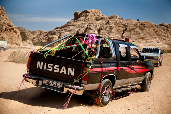 4×4 wedding car decorated with ribbons sets off from tents in desert in Petra to pick up Bedouin bride Ayesha