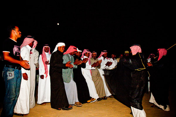 Bedouin men celebrate the wedding by dancing late into the night