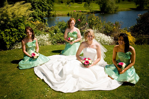 bride with bridesmaids sitting prettily by the lake at Waterton Park Hotel