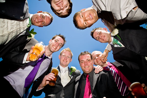 the groomsmen gather around for a wedding pic under the blue sky