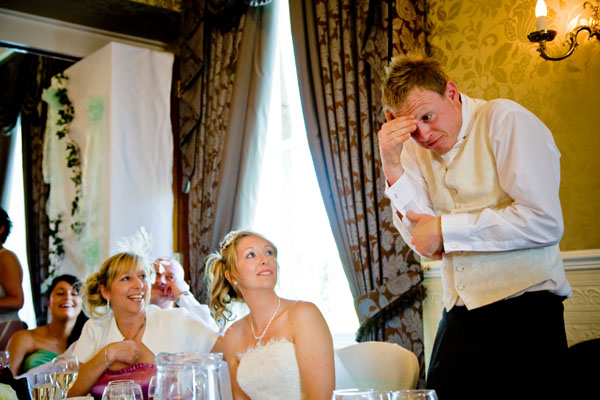 The groom dramatically signs his wedding speech