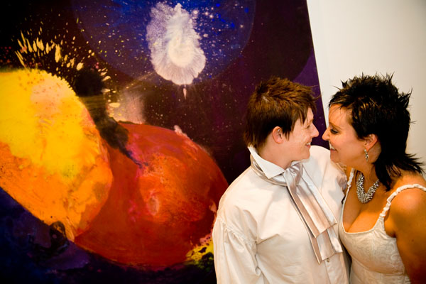 civil partnership couple look lovingly at each other by painting on staircase at the Woodlands in Leeds