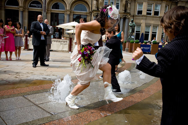 fun picture of bride rushing through the fountains in Leeds city centre