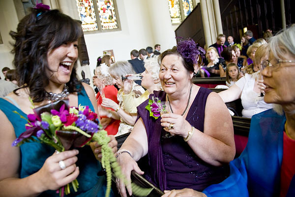 bride's sister talking to her Mum who is drinking champagne in church after the wedding