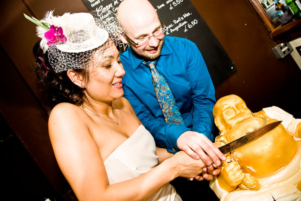 bride and groom cutting their unusual golden Buddha wedding cake