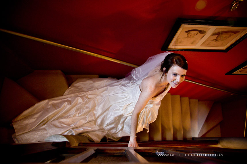 bride on the bridal suite stairs with red wall at Carlton Towers in Yorkshire