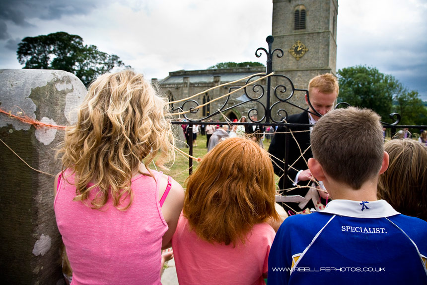Children wait outside Wensley church to await traditional gift of coins