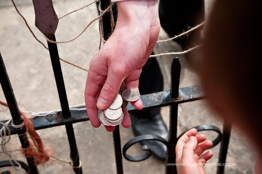 groom hand over coins to eager children's hands outside Wensley Church in  North Yorkshire