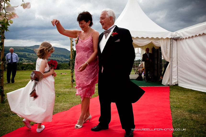 farm marquee wedding picture with bridemaid twirling on red carpet