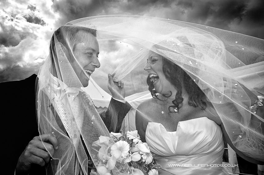 Black and white wedding photos of laughing bride & groom under the veil