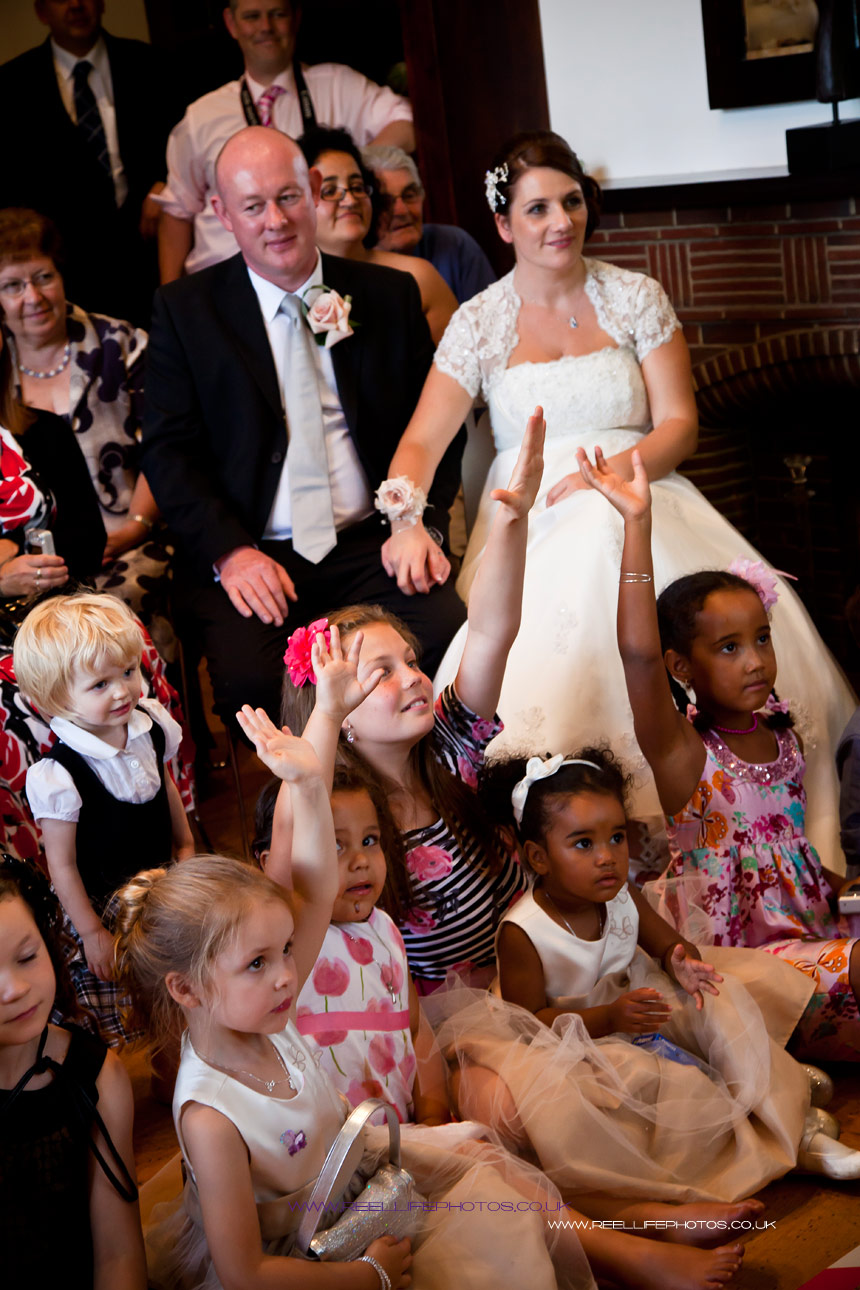 Bride and Groom with children participating in magic show