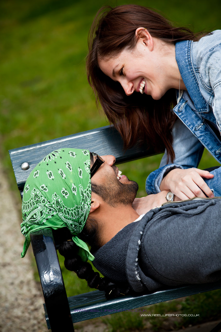 Engaged couple look lovingly at each other on a park bench in Sheffield