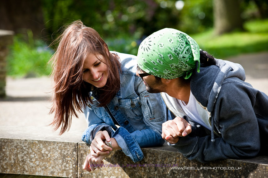 engaged couple leaning over a fountain basin in park in Sheffield