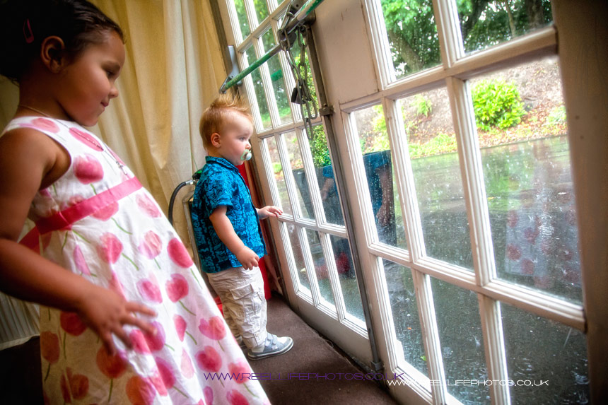 Rainy day wedding with children watching the splashing raindrops through a window