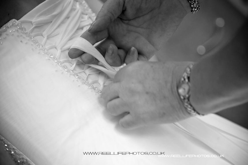 bride's mum lacing her into her wedding dress