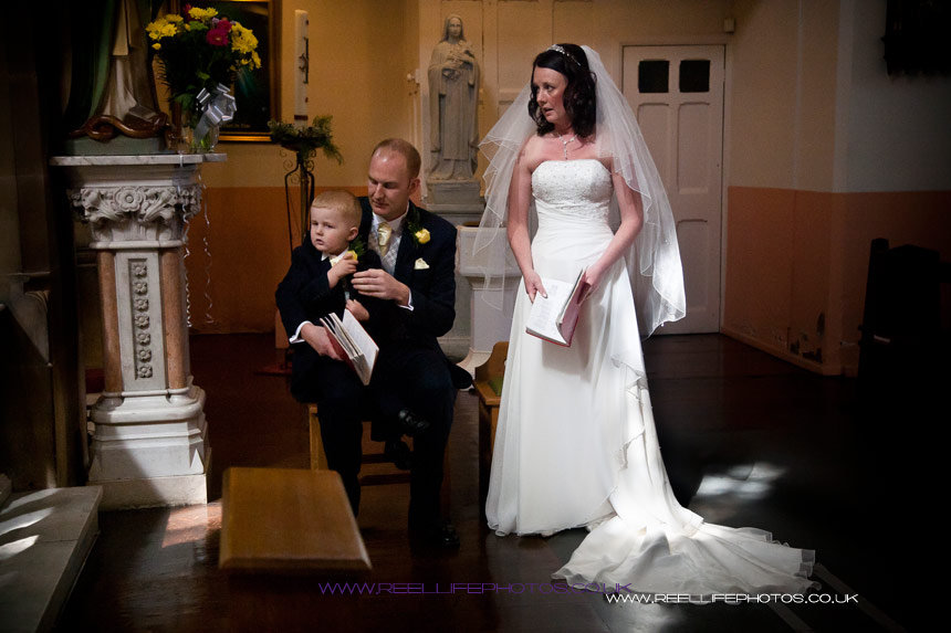 pageboy son joins bride and groom during church wedding ceremony