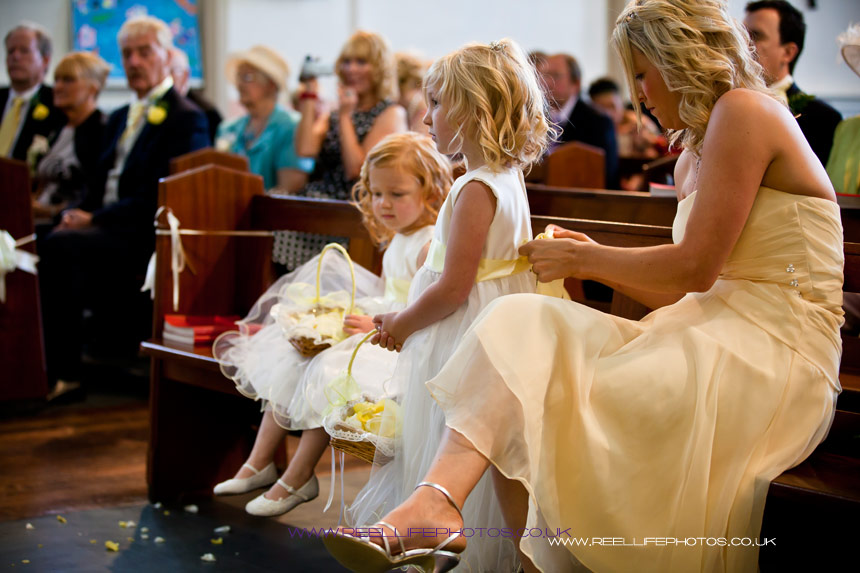 maid of honour ties the flowergirl's ribbon